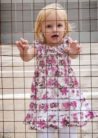 Little girl in a dress behind bars Stock Photo - 8060303
