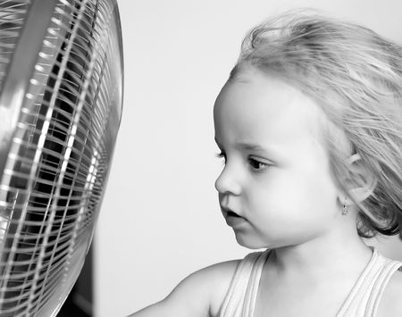 A little girl standing in front of fan photo