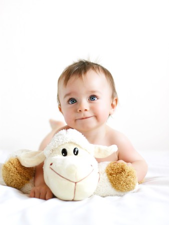 plush toy: Little boy playing with a lamb Stock Photo