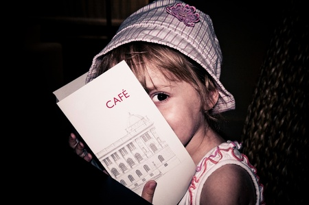 Little girl sitting in a cafe and reading the menu