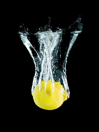 The lemon falling into water . Stock Photo
