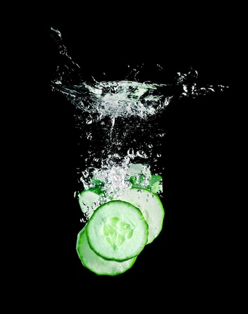 The cucumber slices falling into water . Stock Photo