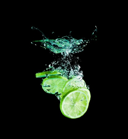 The lime slices falling into water . Stock Photo