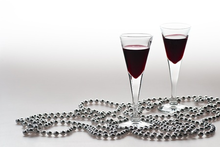 Two glasses wine and silver pearls . photo