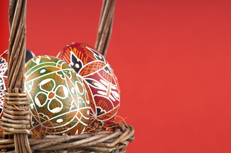 The wicker basket and Easter painted eggs .   photo