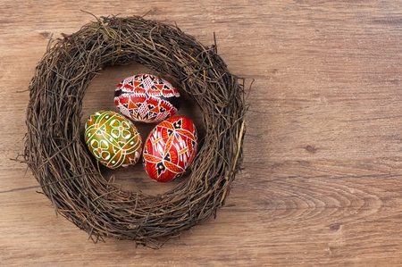 The painted eggs in the nest on wooden background photo