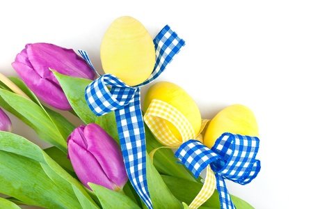 Three yellow eggs, blue bow and tulip flowers  photo