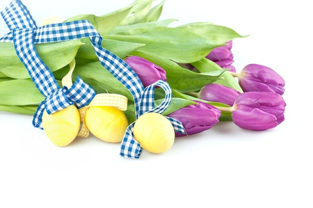 Three yellow eggs with purple tulip flowers  photo