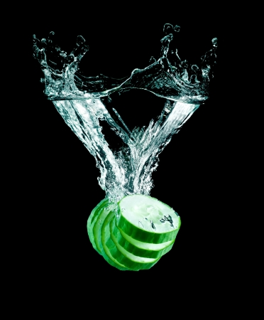The cucumber slices falling into water . photo
