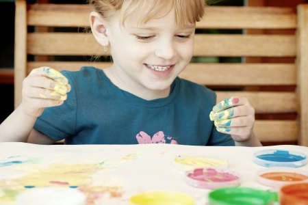 Little girl painting colors on hand photo