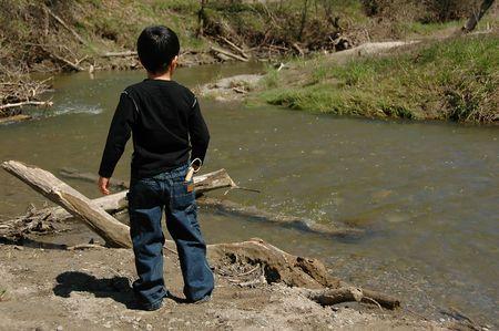 Boy playing near a river Stock Photo