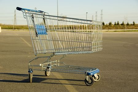 Shopping Cart sitting alone in a parking lot photo
