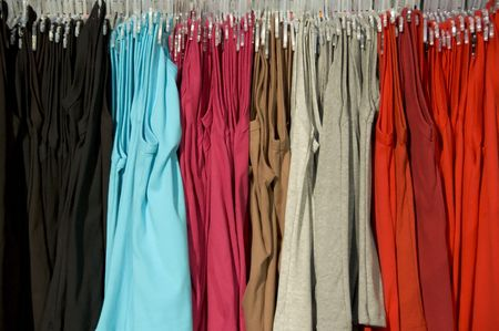 hangers: Rack of clothes on hangers with a variety of colours Stock Photo
