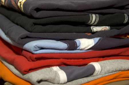 Pile of folded clothes with different colours Stock Photo