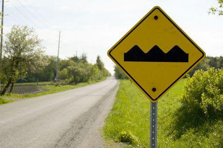 bumpy: Yellow caution sign warning bumpy road ahead Stock Photo