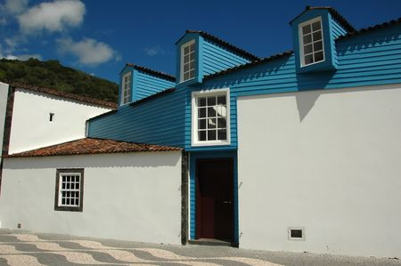 Typical Azores residence architecture against a blue sky on a cobblestone path Stock Photo