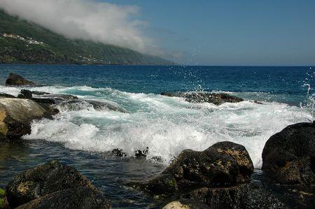 Ocean waves spraying against an Azores Island coastline