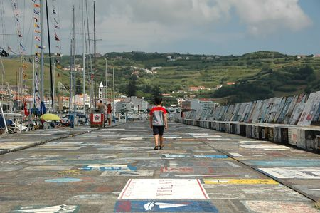 A boy takes a walk down a marina pathway in the Azores