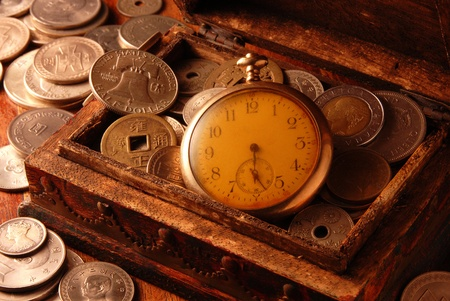 Time is money concept with  old pocket watch and coins photo