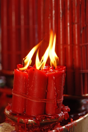A burning flame of a candle of red color photo