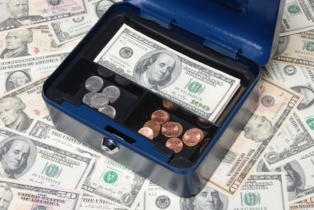 Open safe box with cash and coins.  photo