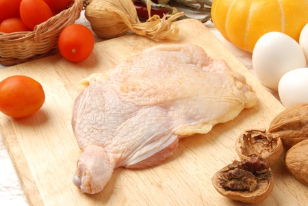 Raw chicken thigh on a wooden cutting board  photo