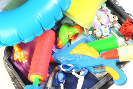Open suitcase with water gun  and toy and beach items Stock Photo