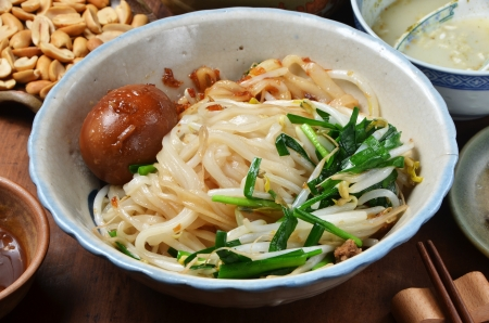 mian: A bowl of dry noodles  on wood table