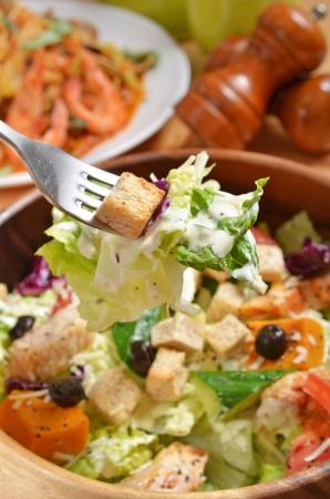 ensalada cesar: Un bocado de ensalada en un tenedor de plata Foto de archivo
