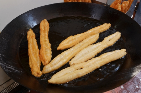 Deep fried  Chinese fried bread stick   in hot oil photo