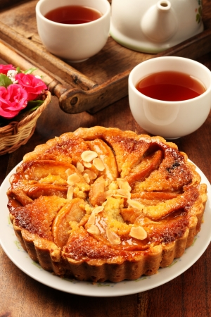 Freshly baked hot apple pie served on a yellow plate with tea     photo