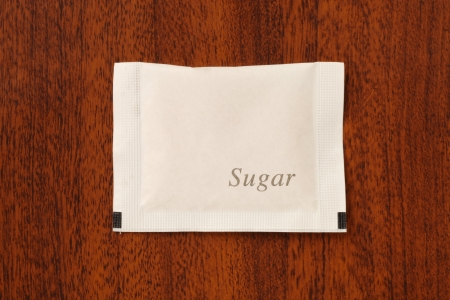 sweetening: Sugar packet on the wooden table