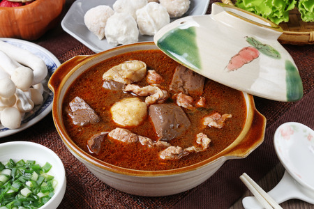 Spicy  hot pot with pork, tofu,  mushrooms and green leaves Foto de archivo