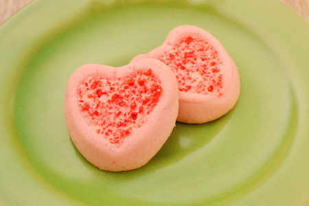 strew: Strew berry heart cookies  on green plate Stock Photo