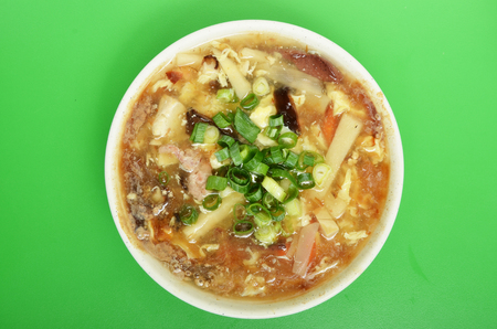hot soup: A bowl of hot and sour soup on green background. Stock Photo