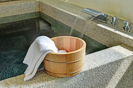 bañarse: cubo de baño con una toalla en un baño de aguas termales en el onsen japonés
