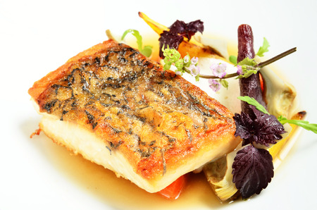 seafood: Grilled striped bass and vegetables on white plate. Stock Photo