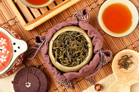 chinese food: Tea caddy and Chinese tea set on wooden table Stock Photo