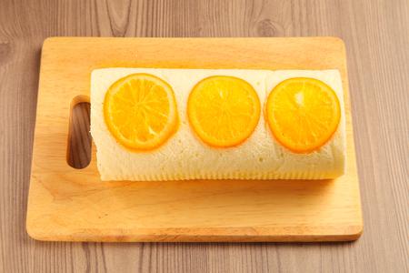 swiss roll: Orange swiss roll on the wooden cutting board