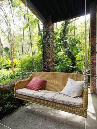 balançoire porche avec des oreillers confortables Banque d'images