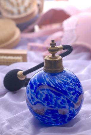 perfume spray: Perfume spray bottle on a fabric background.