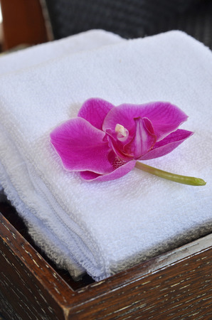 bath: SPA concept: stack of white towels with orchid flower in the wooden tray