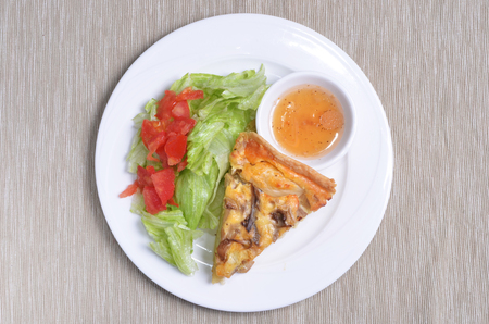 A slice of wild mushrooms and cheese quiche lorraine with salad served on a white plate