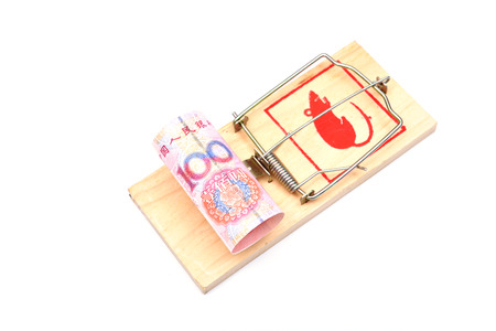 Roll of one hundred chinese yuan banknotes in a mousetrap isolated on white background