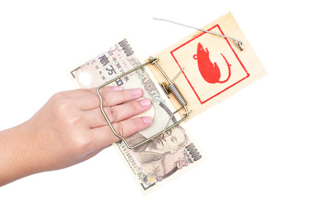 People hand trapped while catching the money put on the mousetrap Stock Photo