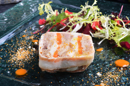 Duck terrine with salad on dark slate Stock Photo