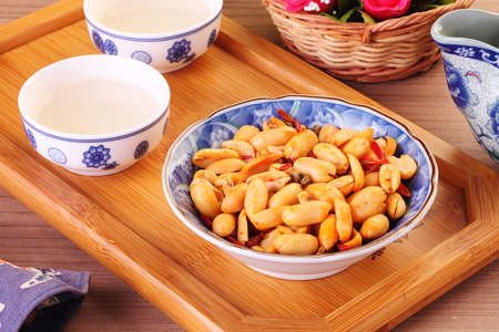 Spicy coated peanuts with tea on the table Stock Photo