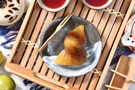 Red bean alkaline zongzi with tea on the table Reklamní fotografie