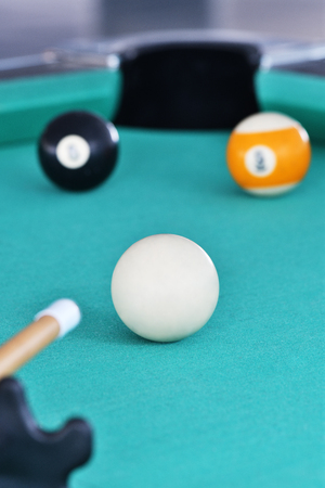 Playing Billiards on green table.