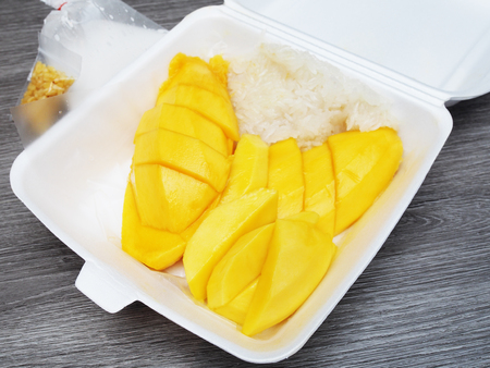 Mango sticky rice in foam box on wood table Imagens